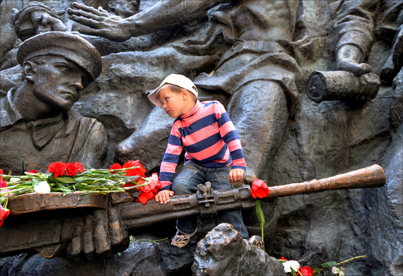 A young boy stares at a statue of USSR soldier as he climbs on a memorial to the Great Patriotic War in Kyiv