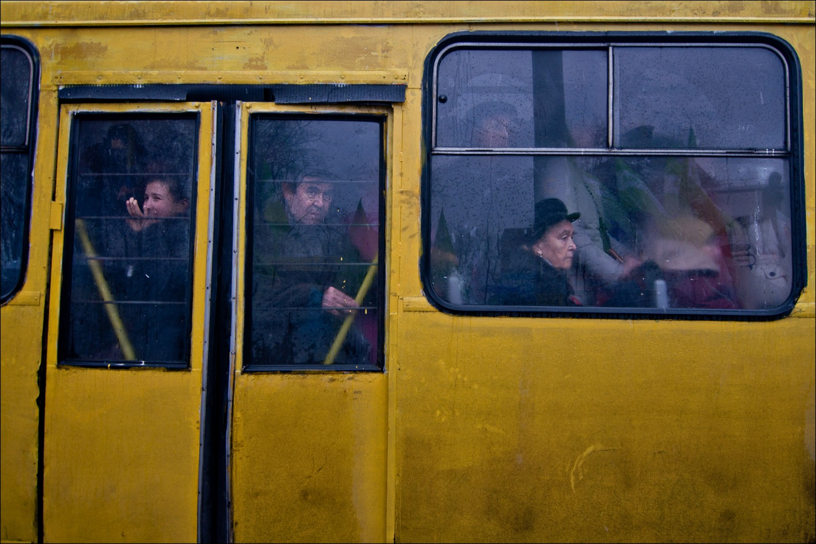 Ukraine: passengers on a crowded bus stare out at an anti-government protest reflected in the window