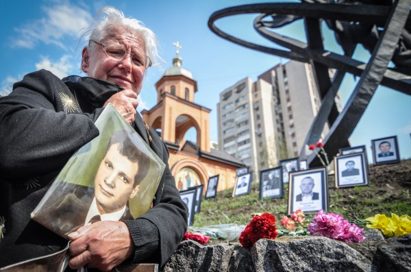 A grieving mother holds a photograph of her son who died while working as a Chernobyl liquidator