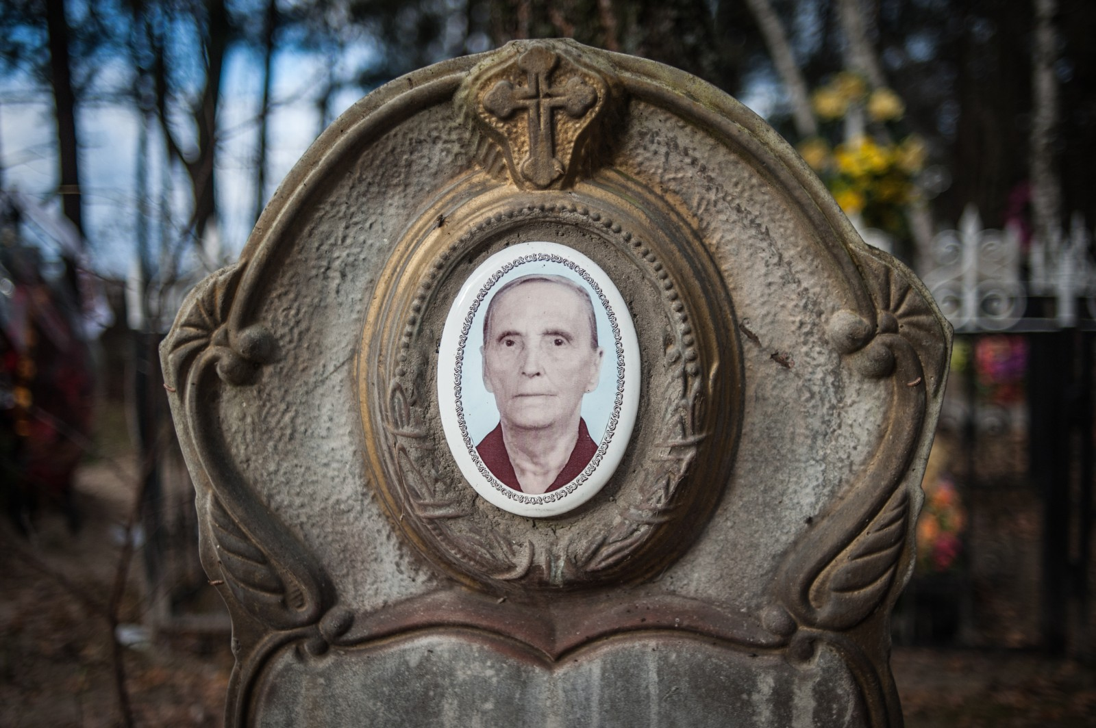 A tombstone with a photograph of the deceased in a cemetery near Chernobyl