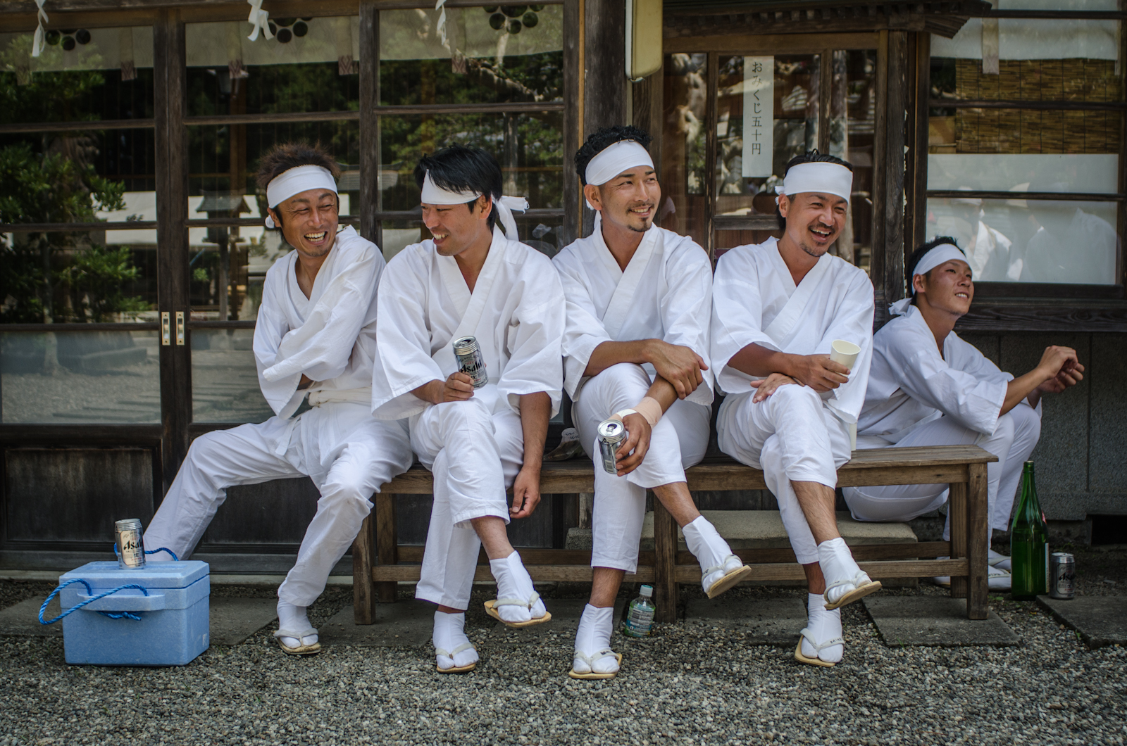A group of young men drink beer before competing to subdue wild horses outside Odaka temple in the Fukushima 'Yellow Zone'