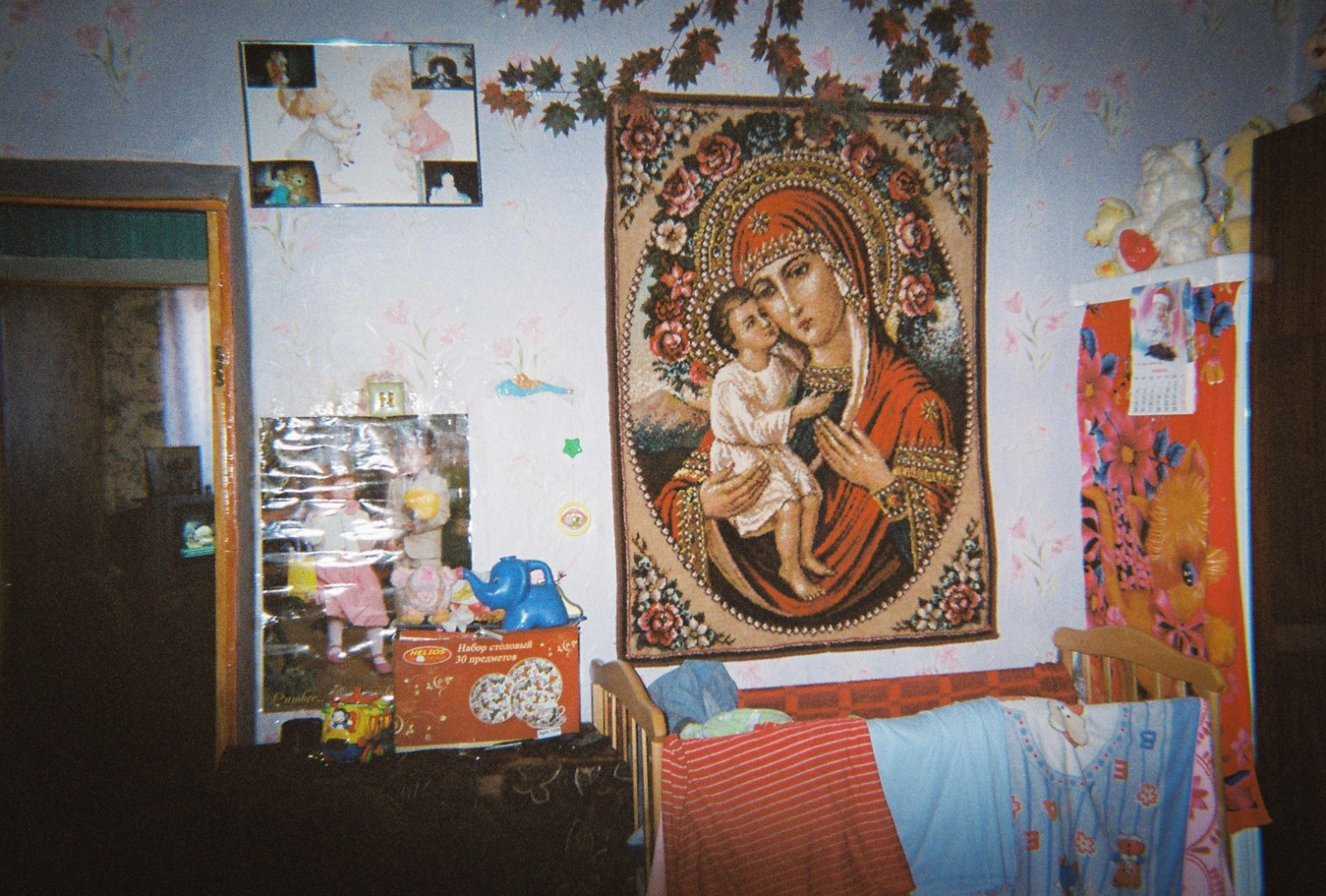 A catholic tapestry is stuck to the wall in a child's bedroom