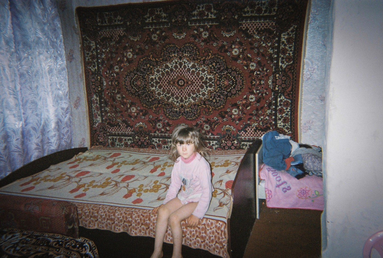 A young girl stares at her mother, who is photographing her sitting on a bed
