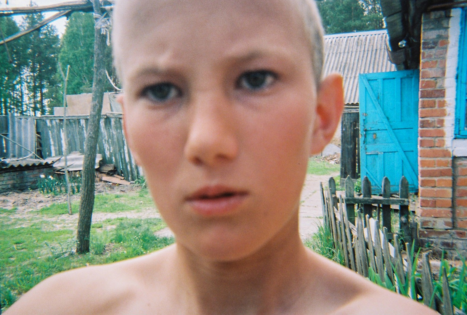 A young boy takes a 'selfie' in outside his house near Chernobyl