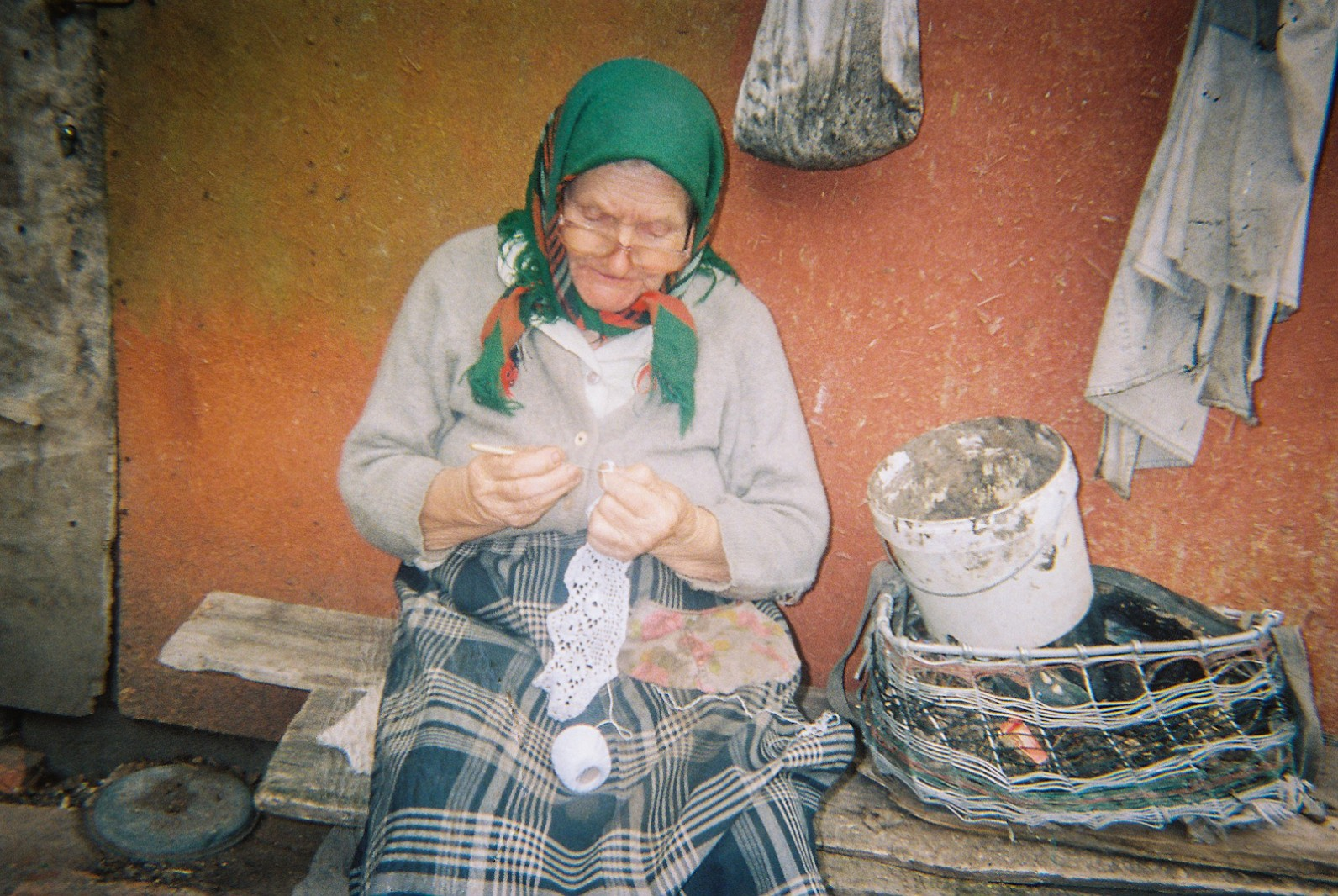 An elderly lady doing embroidery outside her  rural home