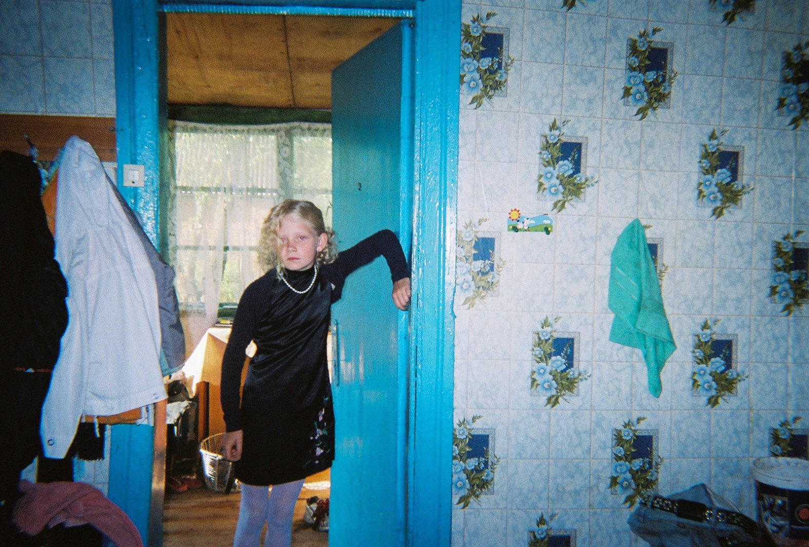 A young girl poses for the camera in her house adjacent to the Chernobyl Exclusion Zone