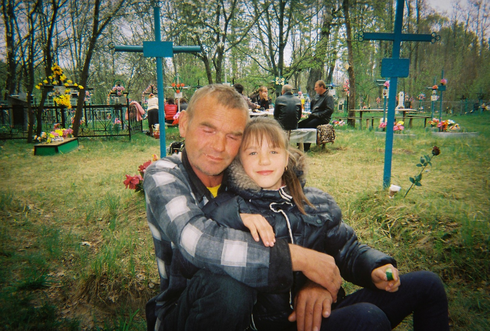 A father and daughter at a local cemetery during Easter celebrations. A table of villagers sit in the background eating and drinking